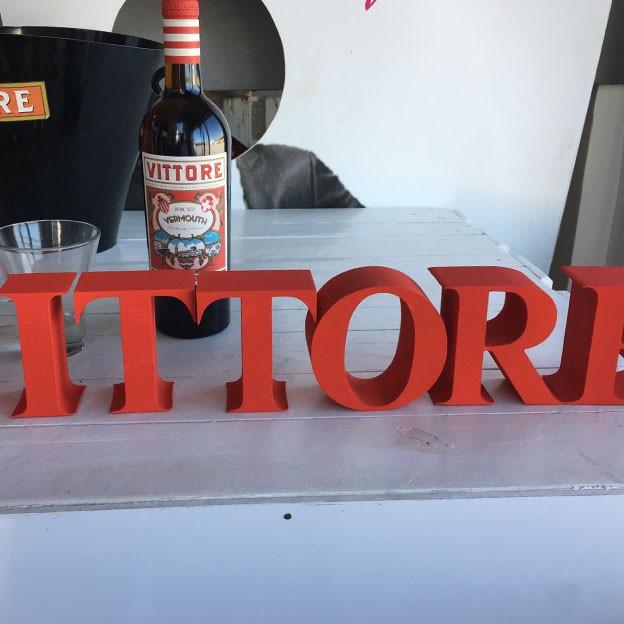 Letras de corcho compacto con tipografía romana clásica y pintadas en rojo para la empresa Vittori